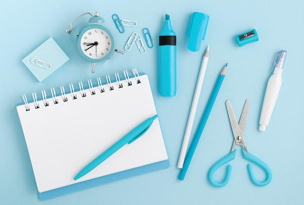 Канцелярские товары, школьные принадлежности и белый пустой блокнот на пастельных синем фоне. вид сверху, макет