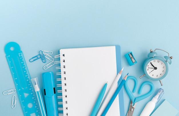 Канцтовары, школьные принадлежности на пастельных синем фоне. вид сверху, макет