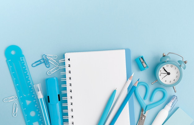 Stationery, school supplies on pastel blue background. top view, mockup