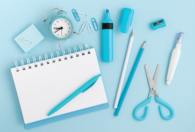 Stationery, school supplies and white blank notepad on pastel blue background. top view, mockup