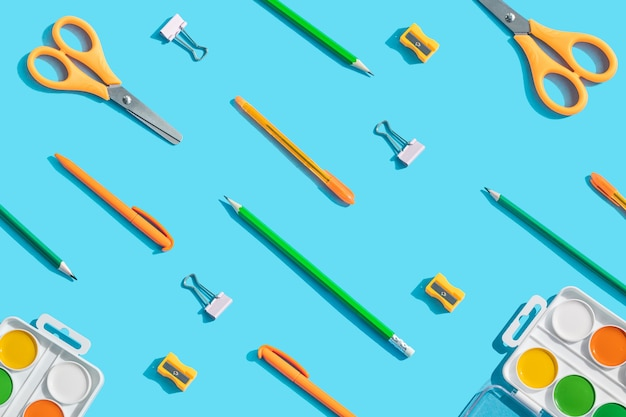 Stationery: scissors, pens, pencils, paper clips, watercolor paints. the concept of learning, children's creativity.  blue background, top view, flat lay.