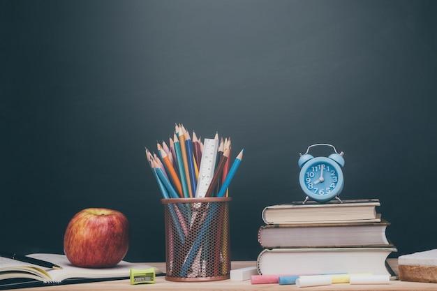 文房具用品とアクセサリーの色チョーク、クレヨン、消しゴム、鉛筆、定規、アップルレッド、本、机の上に置く教室の背景に空白の木製の文房具黒板。学校に戻る教育の概念