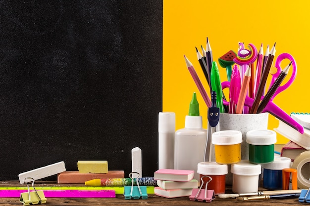 Stationery on a table in front of blackboard