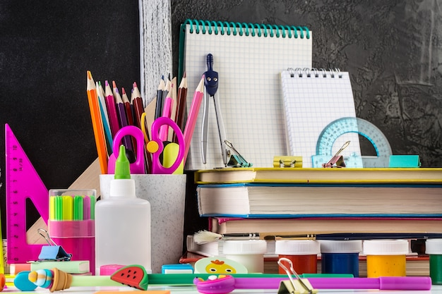 Stationery on a table in front of blackboard.