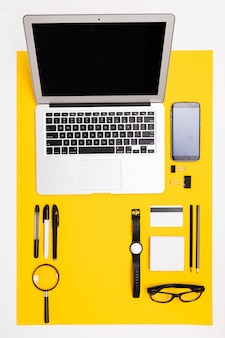 Stationery with laptop, credit card with mockup, phone and magnifying glass lie on the table