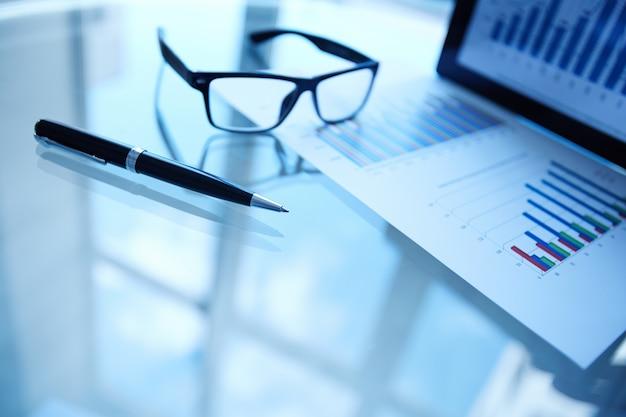 Статистический документ с ручкой и очки