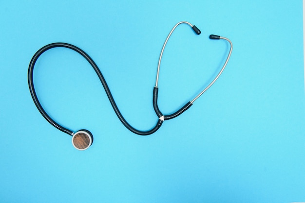 파란색 배경, 평면도에 statoscope 근접 촬영 글로벌 의료 개념입니다. 파란색 배경에 마음으로 statoscope 세련 된 의사입니다.