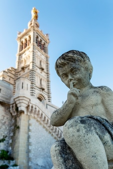 Statue of an angel in the form of a boy against the  of the notre dame cathedral in marseille. vertical.