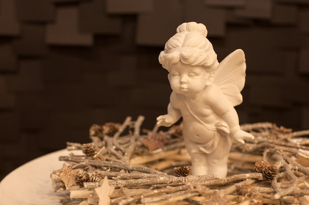 Statue of an angel girl with wings and a wreath of twigs on a dark background for christmas