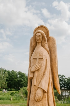 Statue of an angel tree with wings and a cross