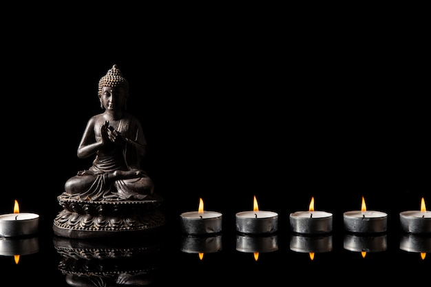 Statue of buddha sitting in meditation, candle line with black copy space