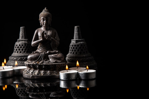 Statue of buddha sitting in meditation, candles, with black copy space