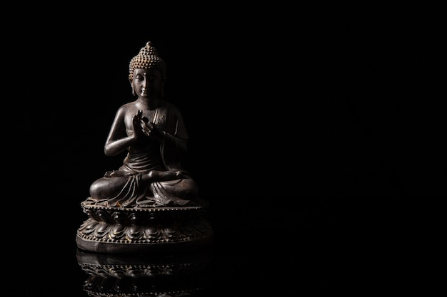 Statue of buddha sitting in meditation with black copy space