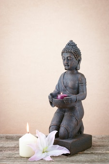 Statue of buddha with a candle his hand on a beige background