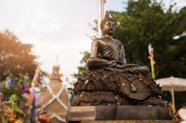 Statue of buddha with sand pagoda background at temple in songkran festival