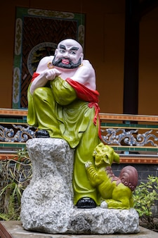 Statue of a buddhist happy man in a chinese temple in the city of danang, vietnam. close up