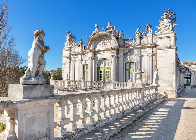 Statue of cupid on a background of the facade of the old royal castle. queluz, sintra.