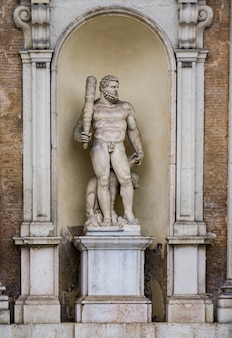 Statue of hercules with a three headed dog at entrance of the ducal palace in modena, italy. sculpure was made by prospero sogari at 1565.
