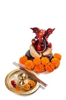 Statue of hindu god ganesha, worship arrangement on white background.