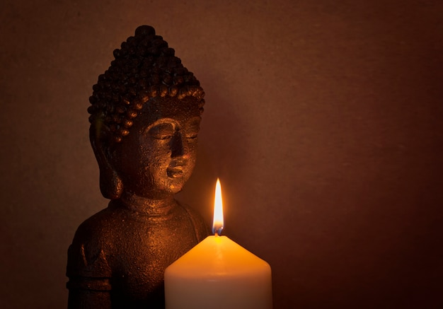 Statue of a holy buddha in the light of a candle
