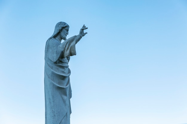 Statue of jesus at notre dame in marseille against a clear blue sky. side view.