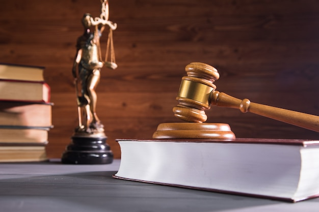 Statue of justice, book and gavel on wooden table