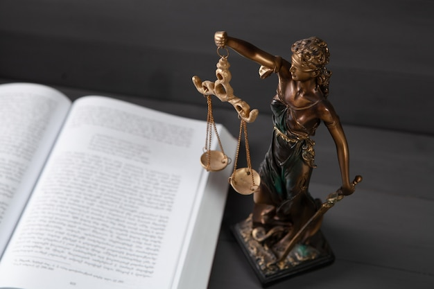 Statue of justice and book on gray surface