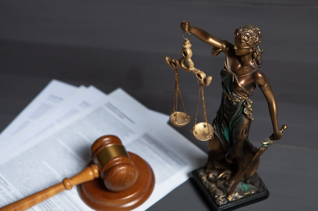 Statue of justice and gavel of judge on gray surface