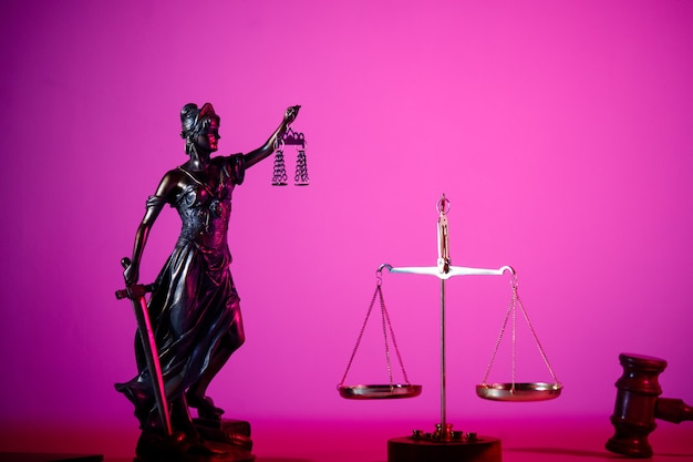 Statue of lady justice on the table in purple neon.