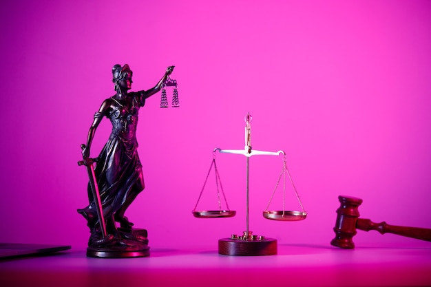 Statue of lady justice with scales on the table in purple neon.