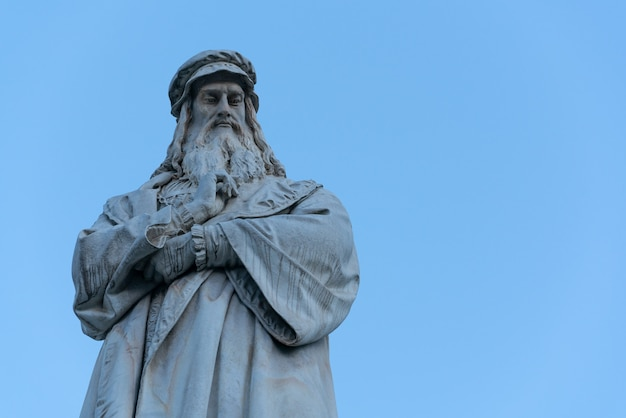 The statue of leonardo da vinci on clear blue sky in milano, italy.