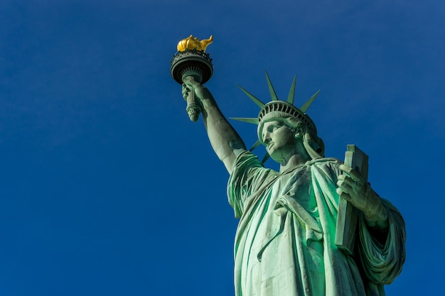 The statue of liberty at liberty island and blue sky background