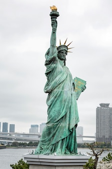 Statue of liberty in tokyo on the island of odaiba in blooming sakura on a gloomy day.