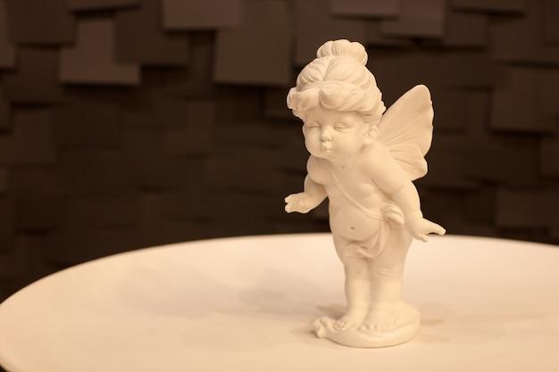 暗い背景の白いプレートに翼を持つ天使の少女の像