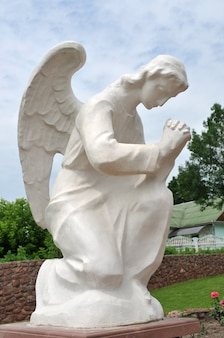 庭で祈りを捧げる天使の像。