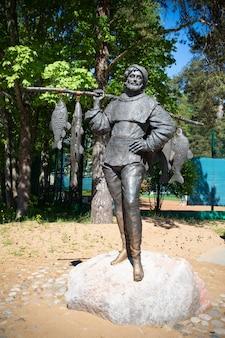 Статуя рыбака с пойманной рыбой в зеленогорском парке в солнечный летний день - санкт-петербург, россия, май 2021 года.