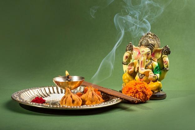 緑の表面に崇拝配置を持つヒンドゥー教の神ガネーシャの像。