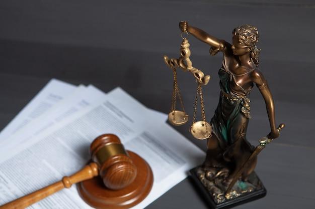 Статуя правосудия и молоток судьи на серой поверхности