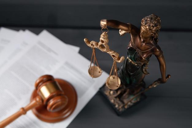 Статуя правосудия и молоток на сером фоне