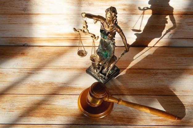 나무 테이블에 정의와 망치의 동상입니다. 시험 개념