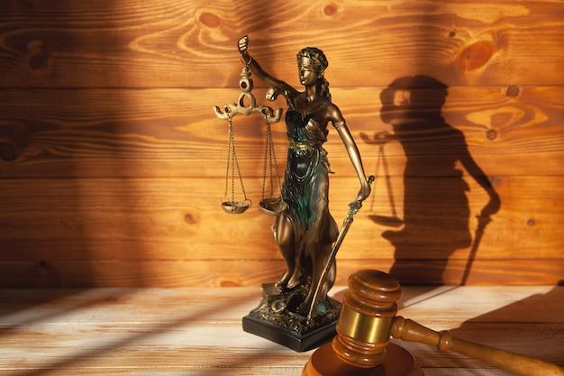 木製のテーブルに正義とガベルの像。トライアルコンセプト