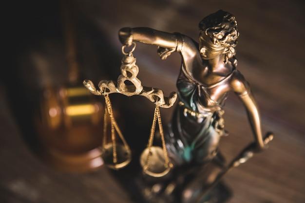 Статуя правосудия и молоток на деревянном столе