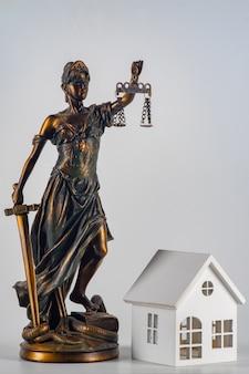 Статуя правосудия и просто минималистичный дизайн с миниатюрным игрушечным домиком на белом фоне. концепция дома мечты по страхованию ипотечного имущества