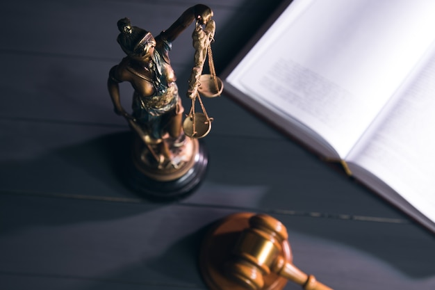 정의, 책 및 나무 테이블에 망치의 동상