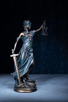 暗い背景に正義の像。法律の概念。