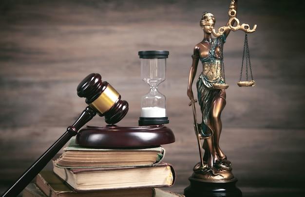 Статуя леди правосудия, песочные часы, книга и молоток.