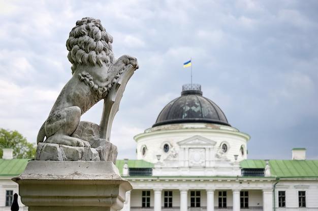 Статуя льва держит щит в лапах. царственный лев опирается на пустой геральдический щит у входа в замок