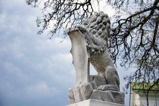 Статуя льва держит щит в лапах