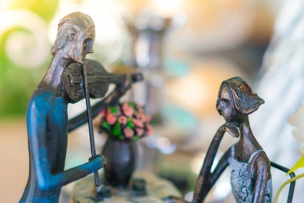 여자와 바이올린을 연주하는 남자의 동상입니다.