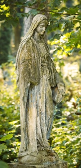 Статуя богородицы марии, на фоне осеннего дерева